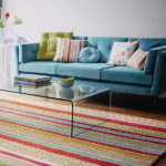 Canapea din catifea turcoaz si covor din lana englezeasca in dungi colorate