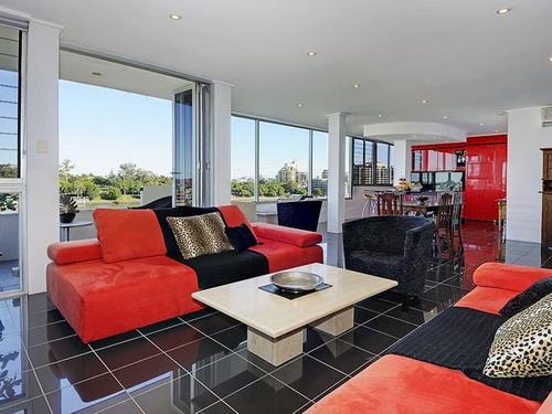 Fotoliu negru si canapea rosie sectionala intr-un apartament contemporan