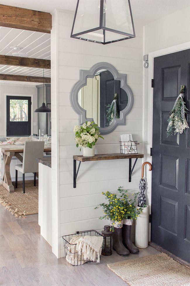 Oglinda cu rama gri deschis si consola suspendata pe perete din hol