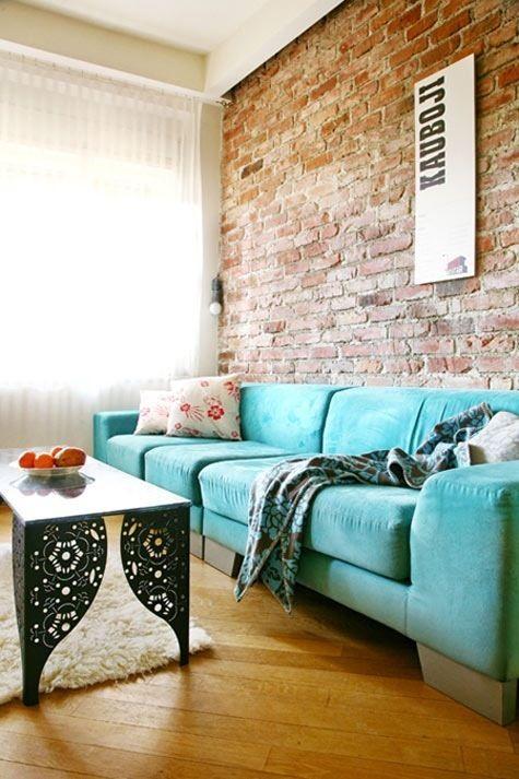 Perete de accent din caramida expusa su canapea turcoaz din catifea