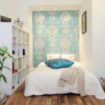 Perete din spatele patului acoperit cu tapet cu model floral