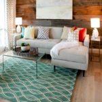Living cu perete placat cu lemn si covor turcoaz