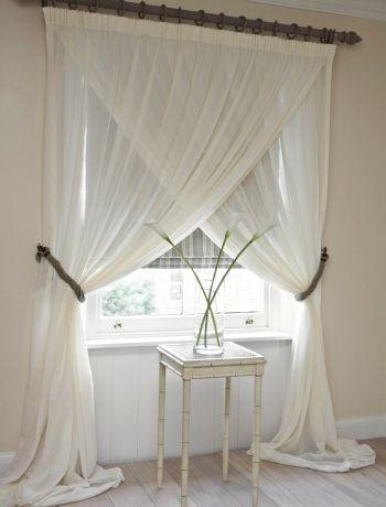 fereastra acoperita cu jaluzea si perdele albe suprapuse