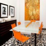 tablou mare intr-o zona de dining cu scaune portocalii