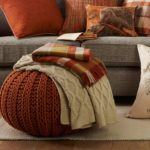 taburet brun si canapea gri cu pernute portocalii