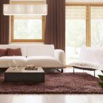 Living casa cu trei dormitoare si mLiving cu canapea alba si covor maro inchisansarda